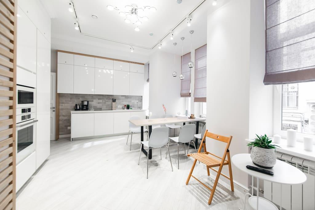 Общий вид кухни. Большой обеденный стол, варочная панель, вытяжка, холодильник, куллер, духовка, посудомоечная машина.