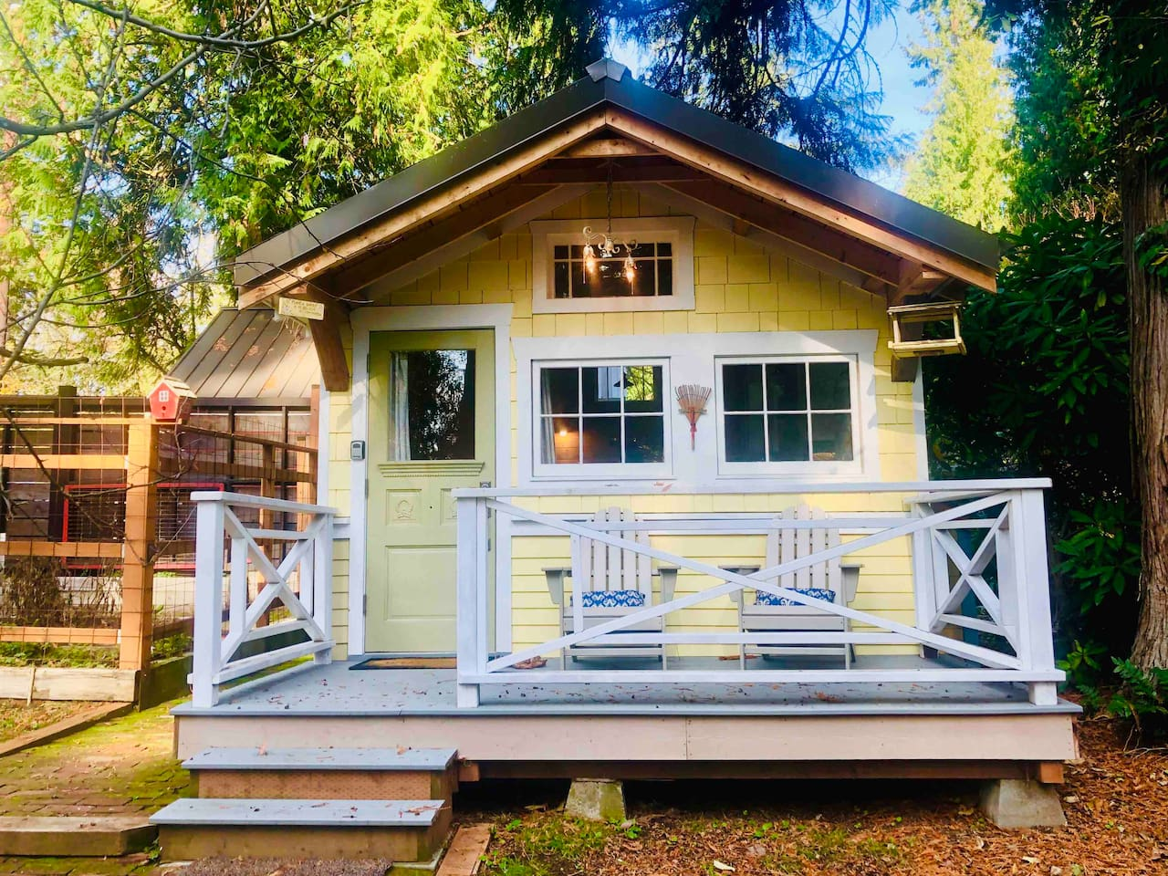 Nestled at the edge of our property under a huge cedar tree, enjoy coffee on your own tiny front porch.  This is a fall view of the tiny house exterior. The cedar trees provide year-round greenery.
