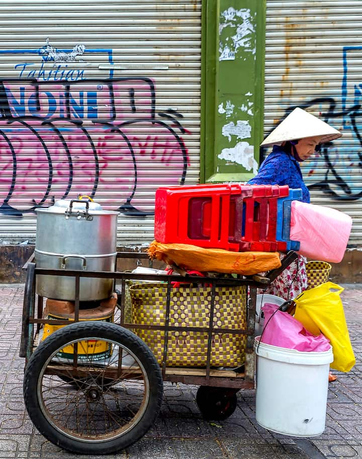 A street food vendor transports her restaurant in Ho Chi Minh City