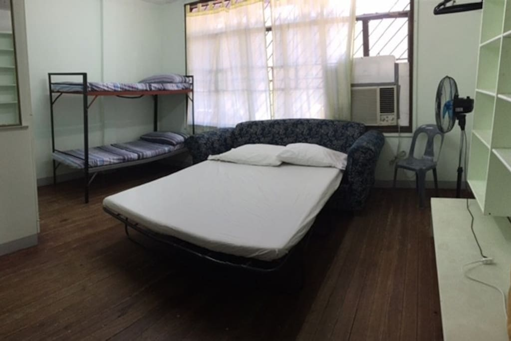 Spacious and clean air-conditioned bedroom with comfortable double bed, study table, and lots of books to read.