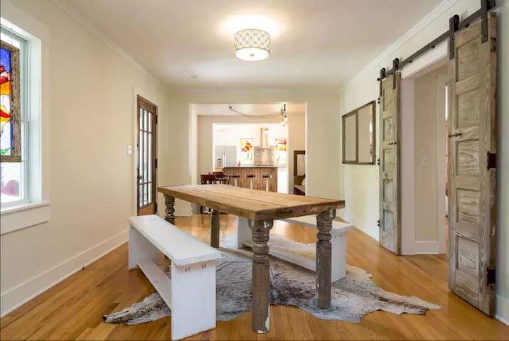 The front entry/dining room has a lovely reclaimed wood table and antique track doors.