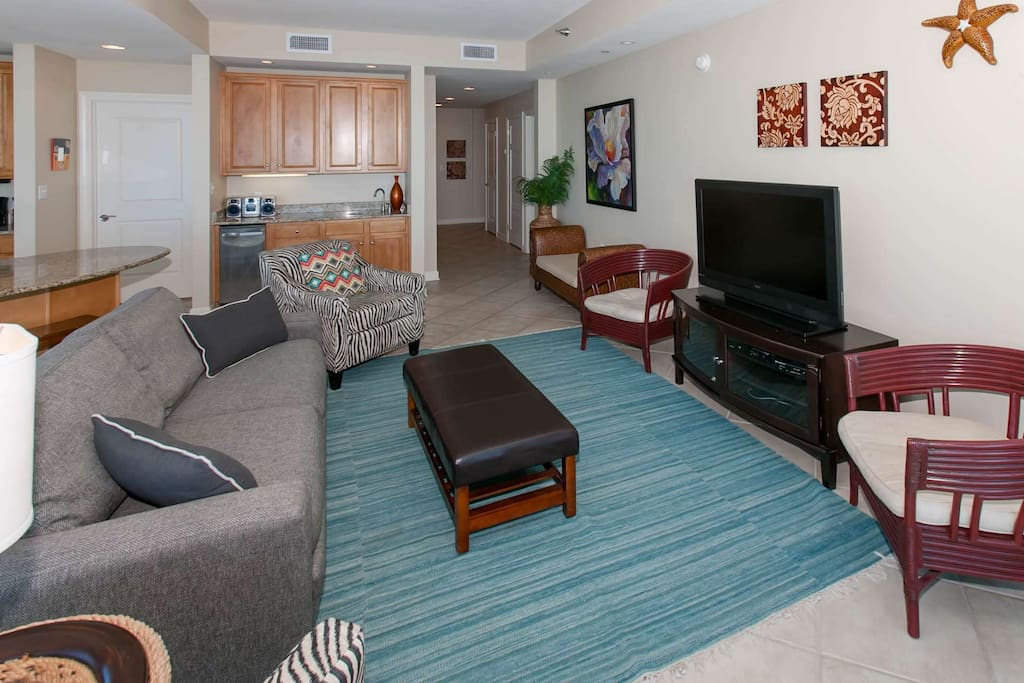 Living room with flat screen TV, looking towards wet bar