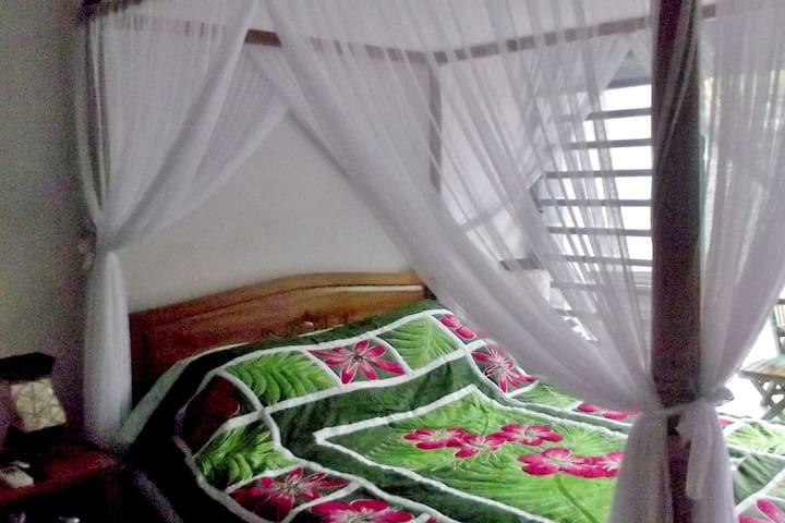 chambre Mait Kaz grand lit avec moustiquaire