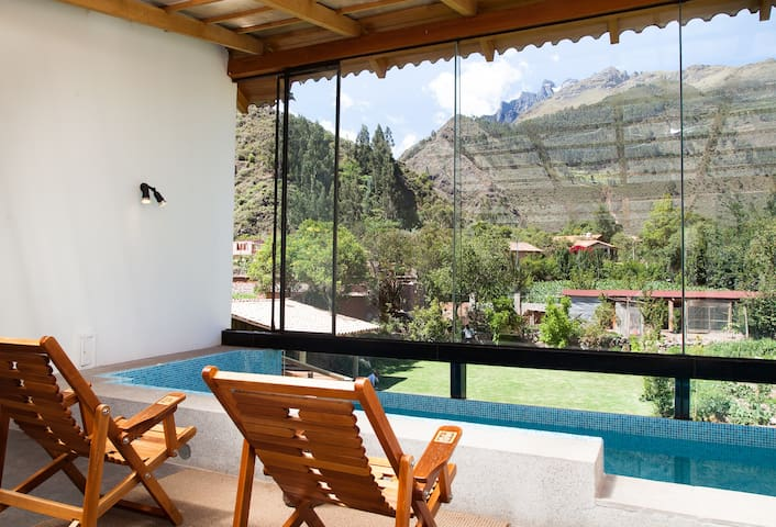 the pool area covered with a glass wall so that the area remains warm to enjoy the pool and cold nights
