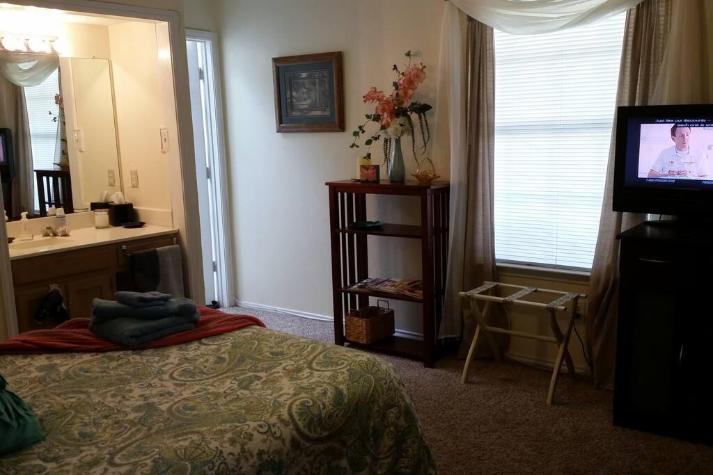 Across the bed to the window, tv, bathroom door and vanity area