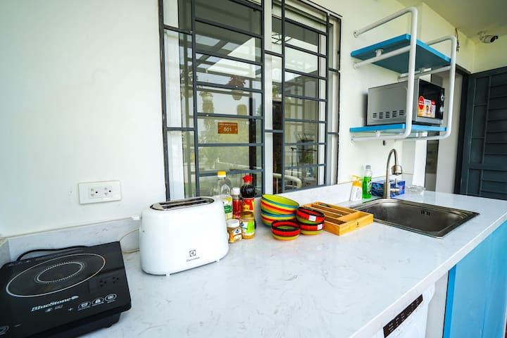 kitchen area w/cooker, toaster, pot & pan, rice cooker and full condiments