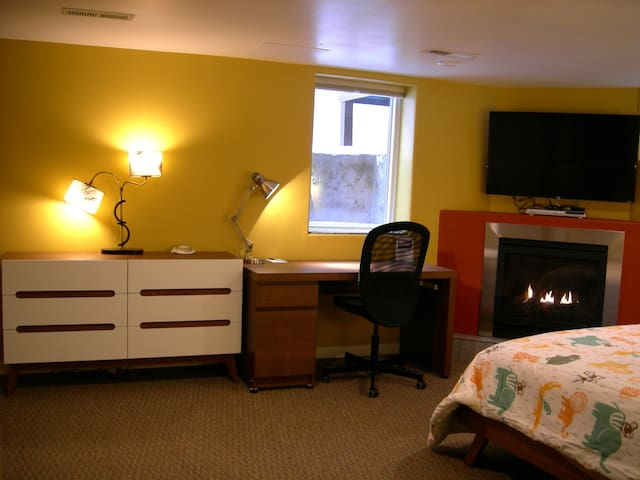 """Queen bed, cozy gas fireplace with 50"""" Smart TV above, dresser, desk and office chair."""