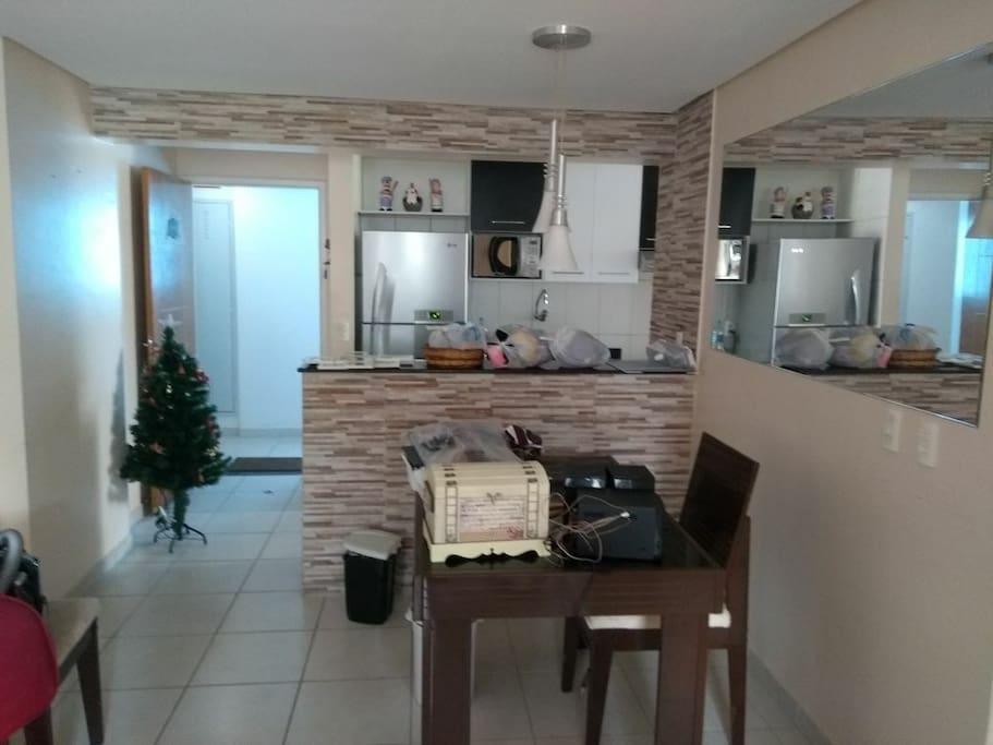 porta de entrada, parte da cozinha com balcão americano e sala