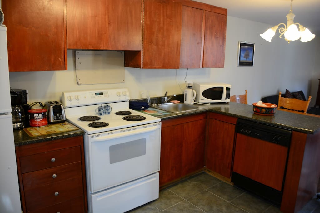 Roomy kitchen with lots of dishes, dishwasher, small appliances of microwave, coffee maker, toaster and kettle