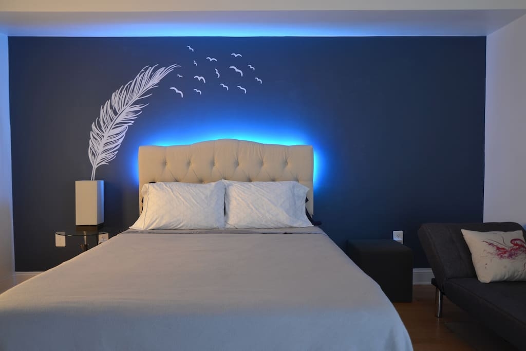 Large Bedroom with queen-size bed, chaise lounge, and custom lighting