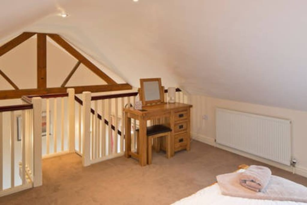 Upstairs open plan bedroom with king size bed