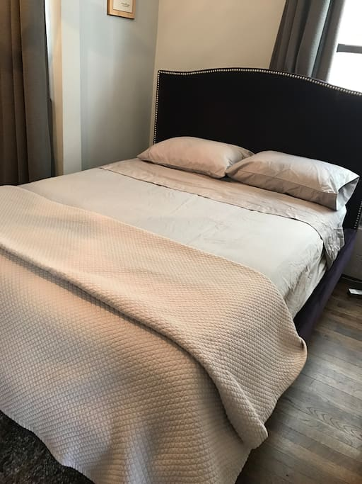 Queen size bed in separate bedroom with quality bed linens and comfy pillows.