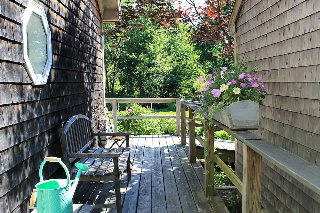 Side entry deck to cottage. Front deck and lawn in background.