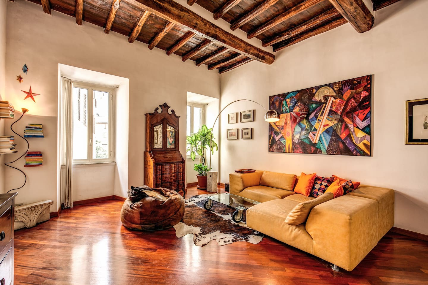 living room with parquet floors and original wooden beams of the 1500 with a super comfortable sofa, TV, antique furniture in fusion with modern style