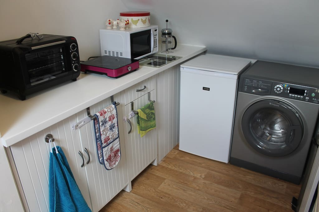 Kitchenette ;induction hob, washing machine, larder fridge, microwave, mini oven and grill, biscuits.