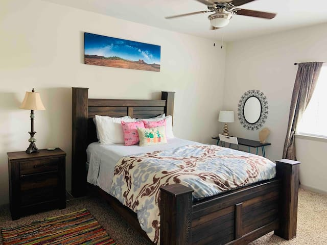 Master bedroom offers a queen bed, hangers, iron, ironing board, with walk in closet and Apple TV.