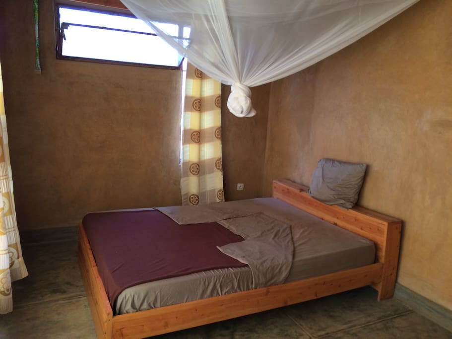 Bedroom 1 - All rooms have queen-sized beds with linens and mosquito nets with closet rods and shelves.