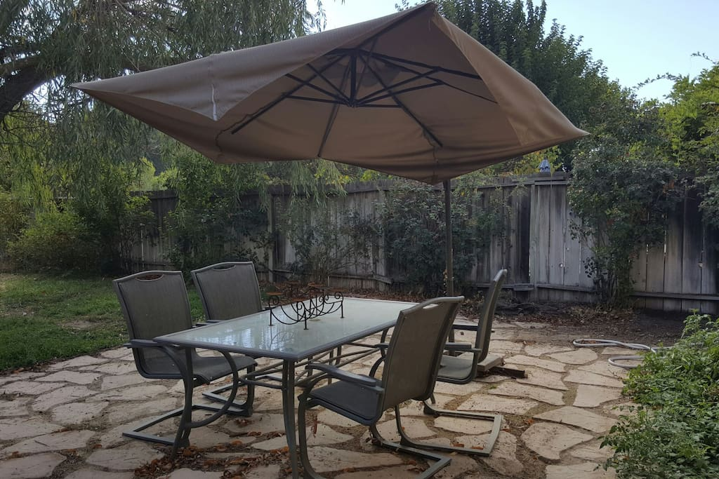 Outdoor dining table with cantilevered umbrella