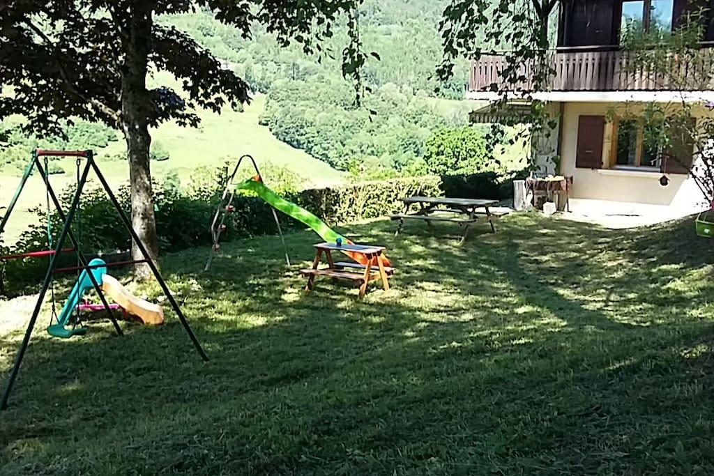 Jardin en jouissance aménagé pour les enfants, table et barbecue pour profiter des belles journées