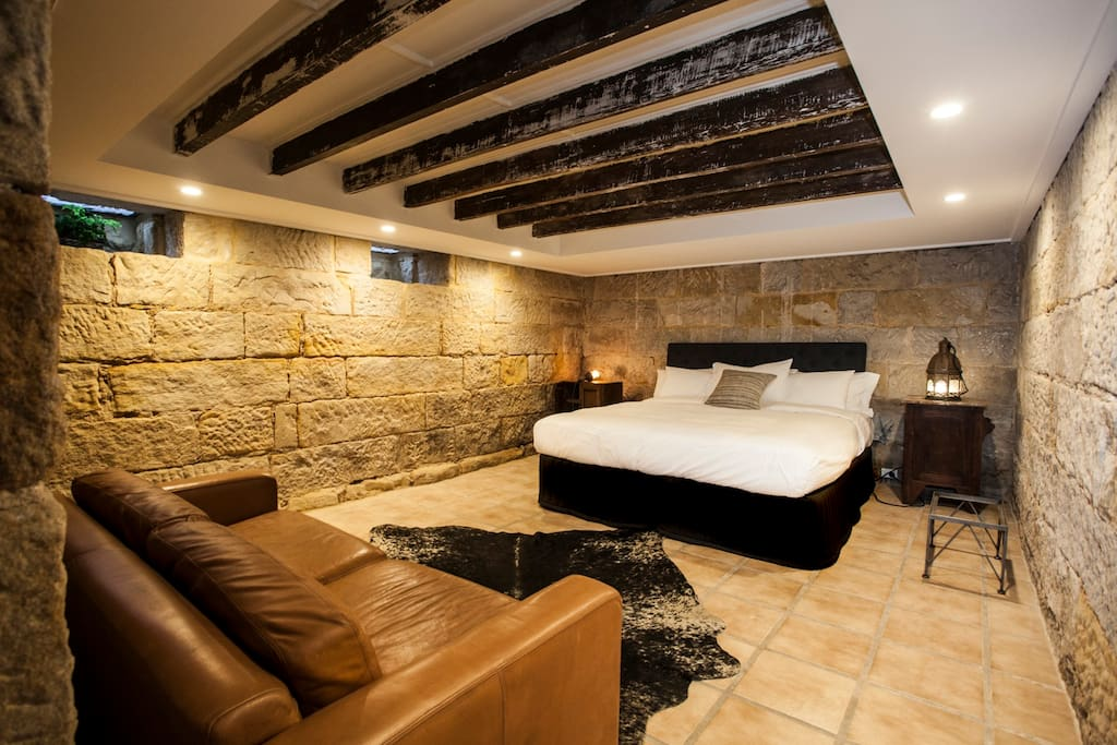 Large king bedroom in sexy, stone room, with lounge.
