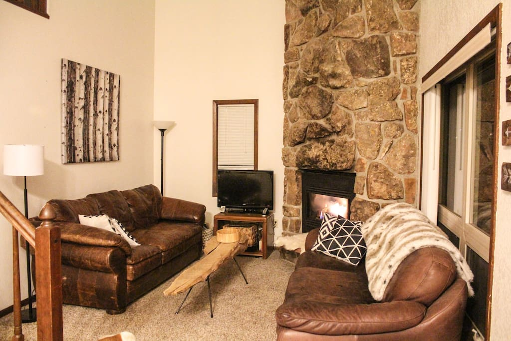 Cozy living room with two leather couches, blankets, and of course gas fireplace controlled by a remote control to keep the place warm.