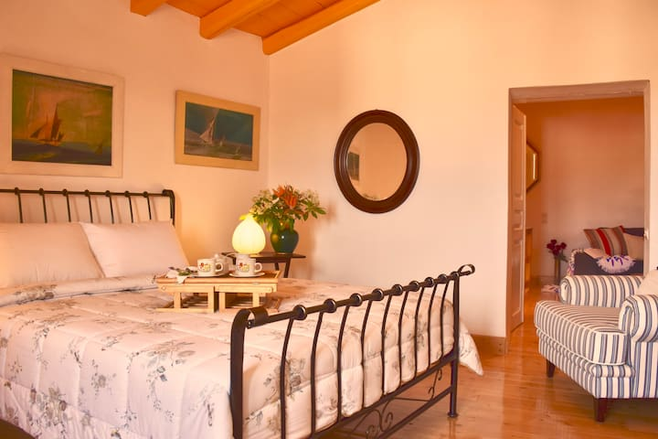 Second floor bedroom with old winery and stables view and a private bathroom..