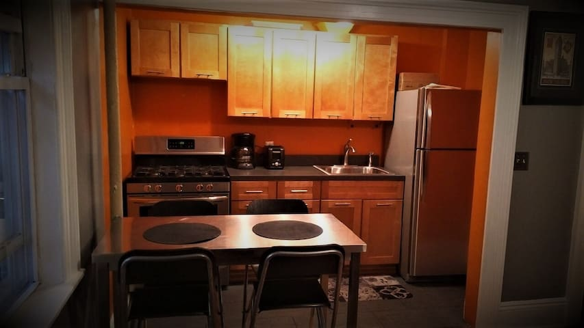 Kitchen with brand new stainless steel stove and refrigerator. High quality tiled flooring.