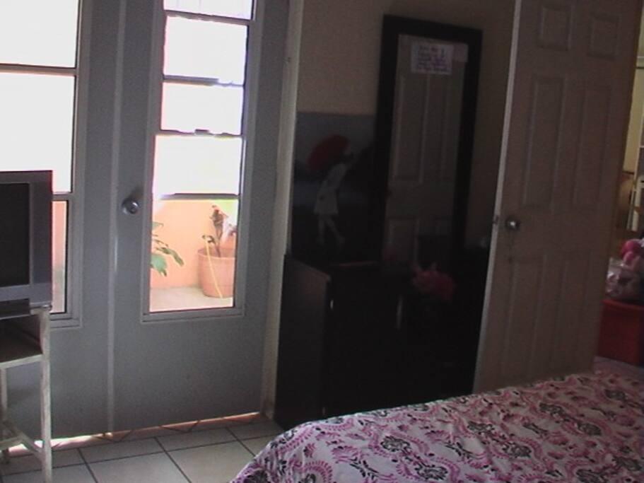 Tocador con espejo con artículos personales. Puerta de acceso a patio interior.