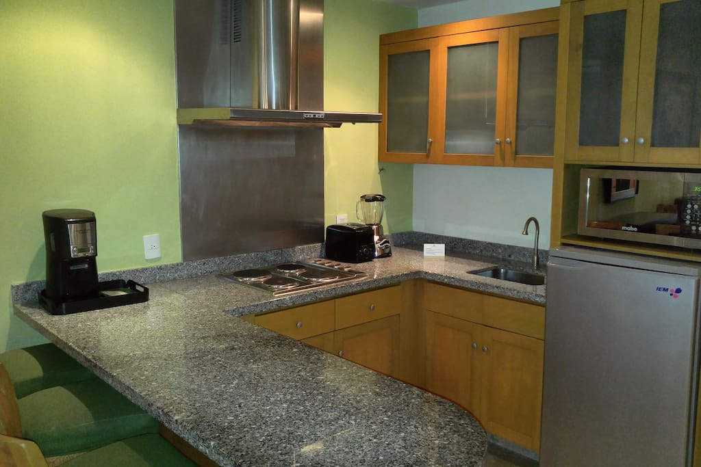 A well-equipped kitchen features granite counters, cooktop, microwave, pots and pans, and full complement of dishes, cutlery and glassware