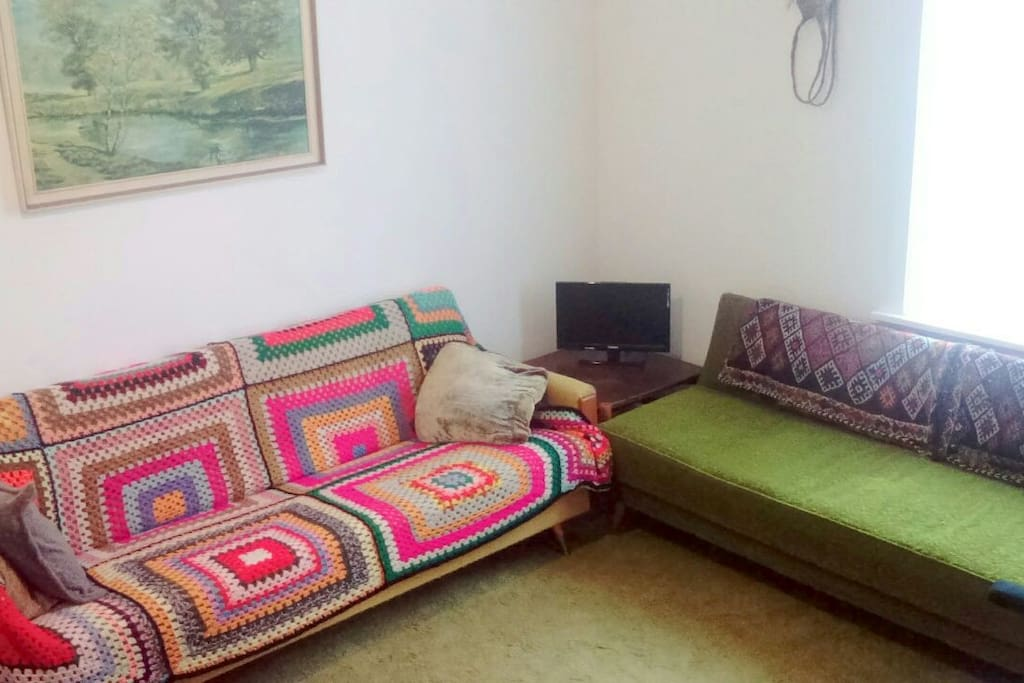 Cozy retro style communal lounge with couple of couches, coffee table, Energy Saver Gas heater pumps out the heat. TV w Freeview channels available.  WiFi.