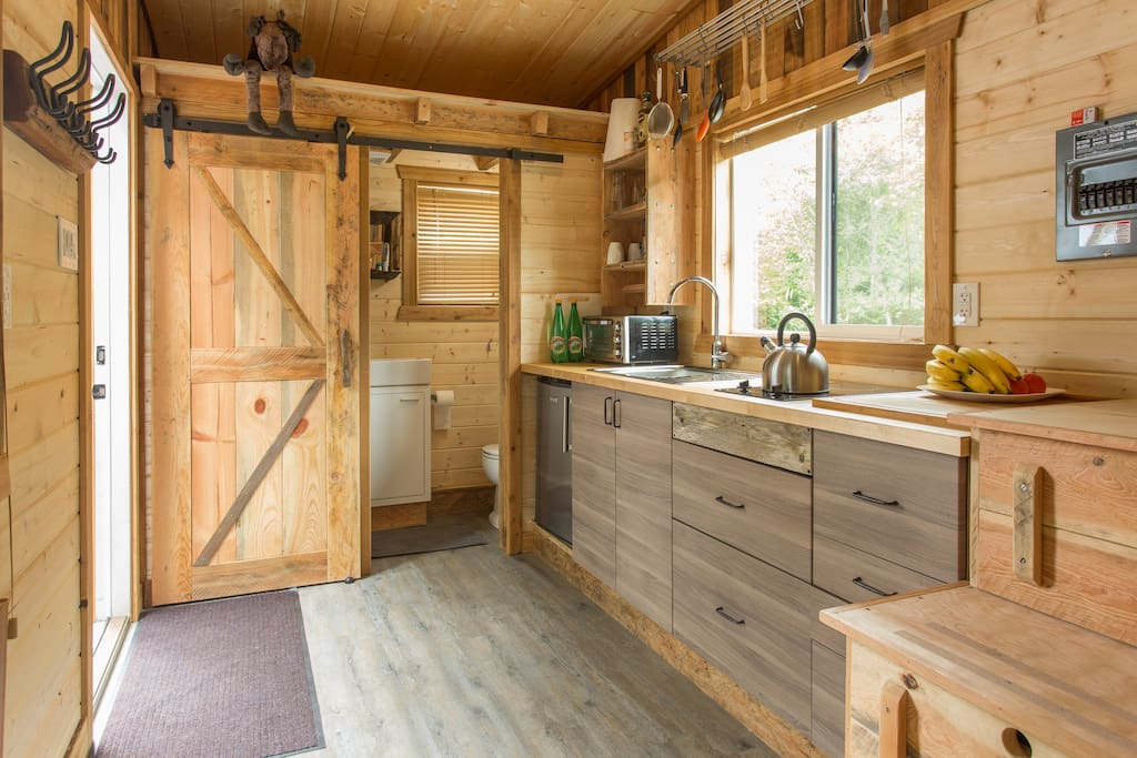Great feeling with all the wood inside the Tiny House. Fridge, two burners and a toaster oven. Bathroom with shower, sink and toilet behind a sliding door.