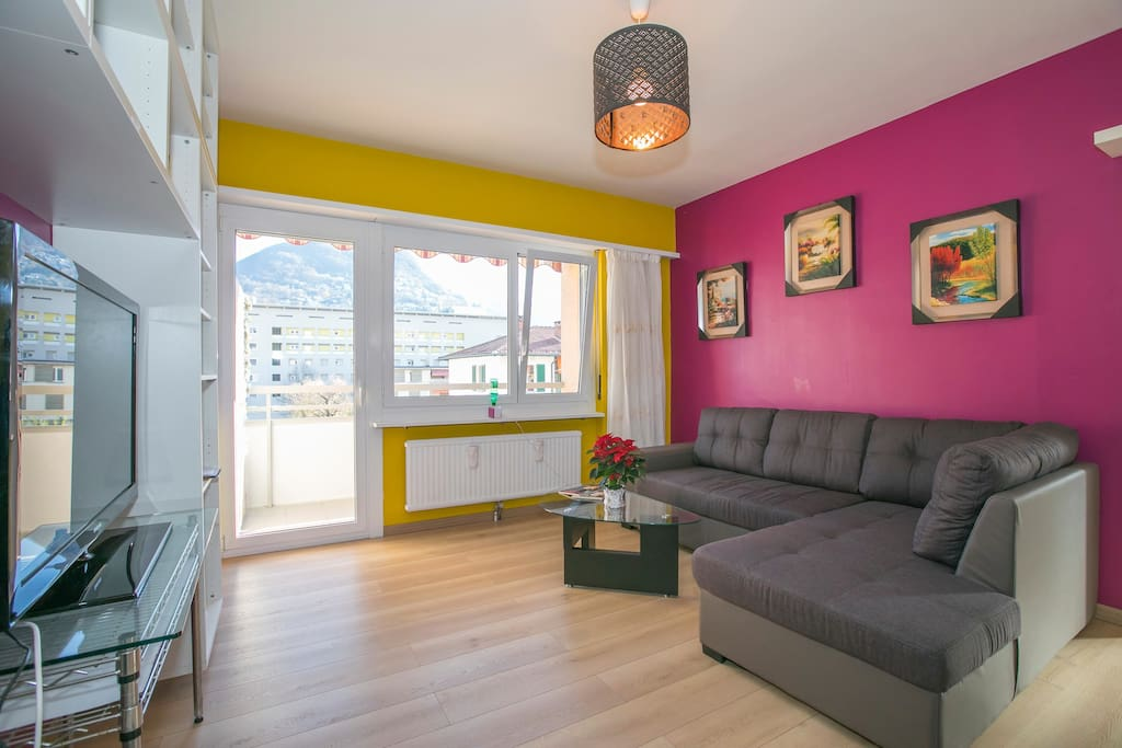 Colorful living room with sleeping sofa and entrance to the balcony