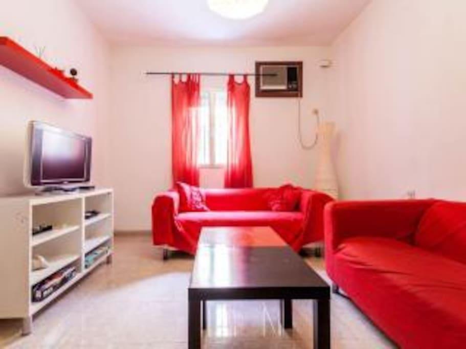 salon con tv ,aire acondicionado ,mesa comedor y sofa cama