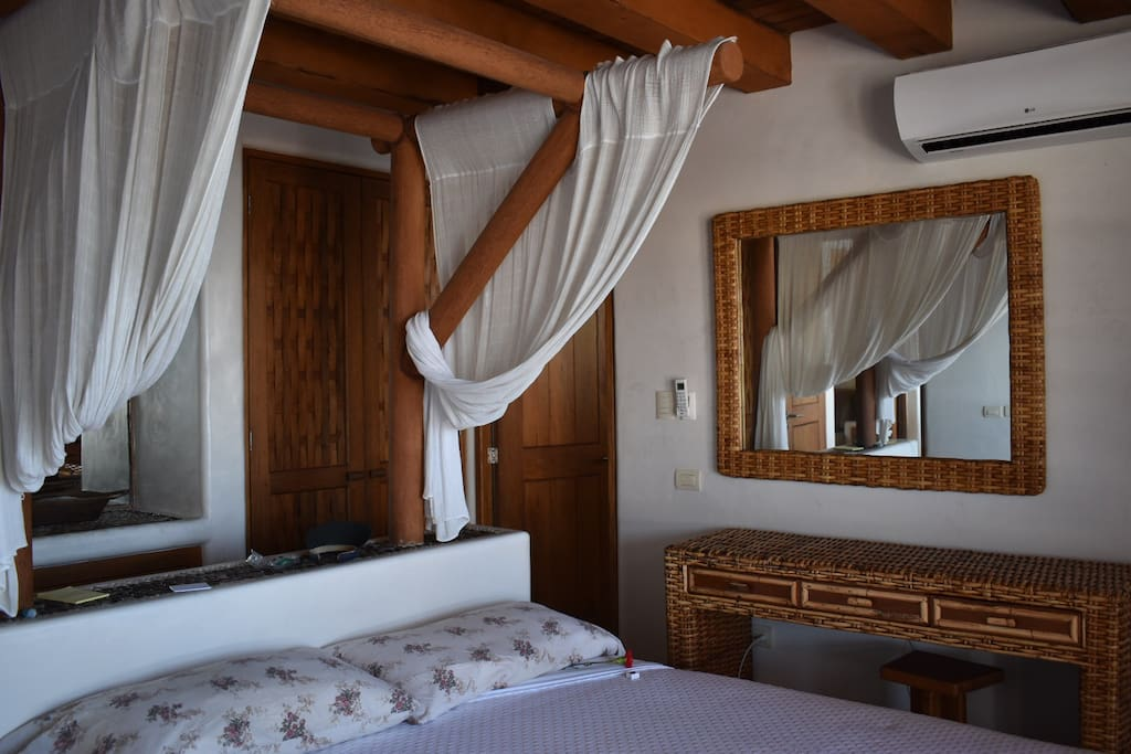 Master Bedroom with dresser and master bathroom, plus large picture windows with screens to listen to the ocean and access to the balcony.