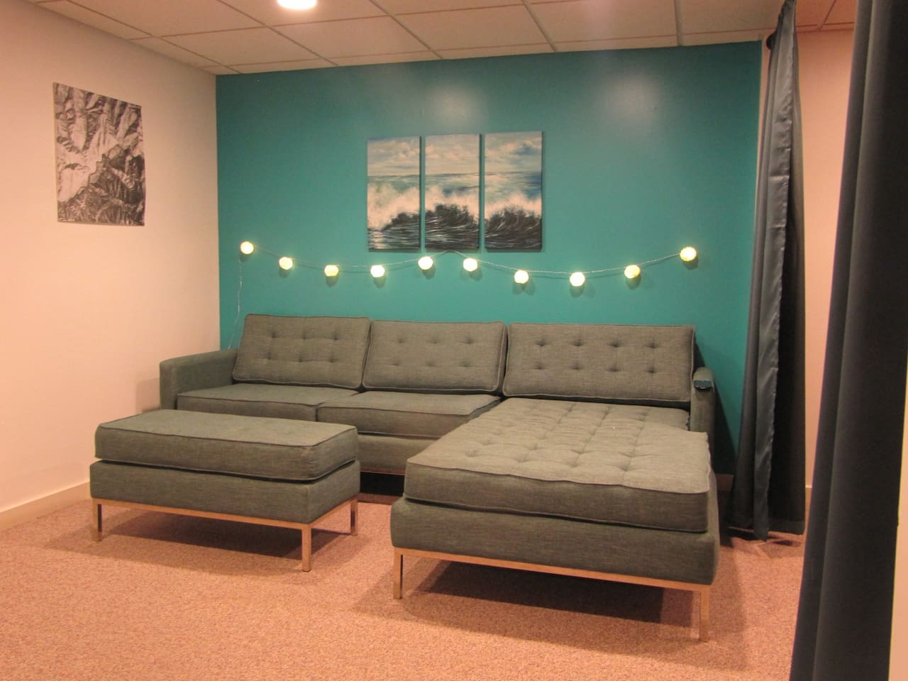 """Freshly painted living room to lounge around. The USA made sectional sofa where an average height person (5'-7"""") may sleep here.  (Sofa does not open, but you can put the ottoman at the end as extension for a taller person.)"""