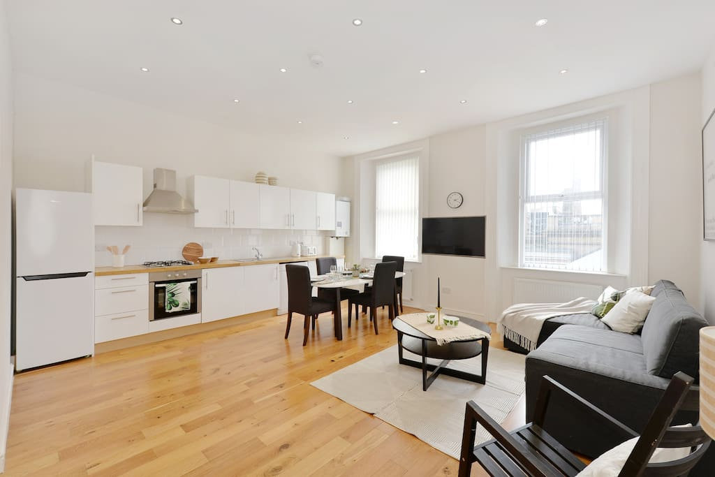 The spacious Living Room with sofa bed, dining table and chairs and well-equipped kitchen