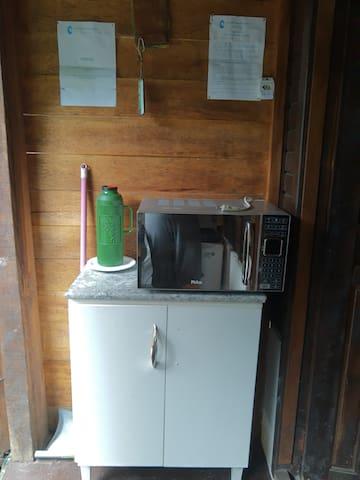 Microondas e armário com ultensilios básicos de cozinha