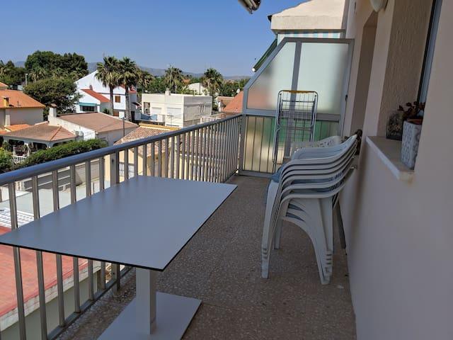 Terrasse avec table, fauteuils et banc. Deux stores.
