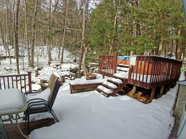 The hot tub is open year round, overlooking a babbling brook