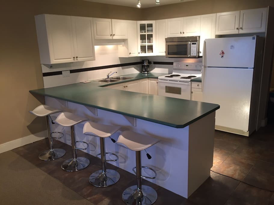 Spacious kitchen with lots of counter space and extra seating. Enjoy the mountain views and visiting with friends and family while in the kitchen.