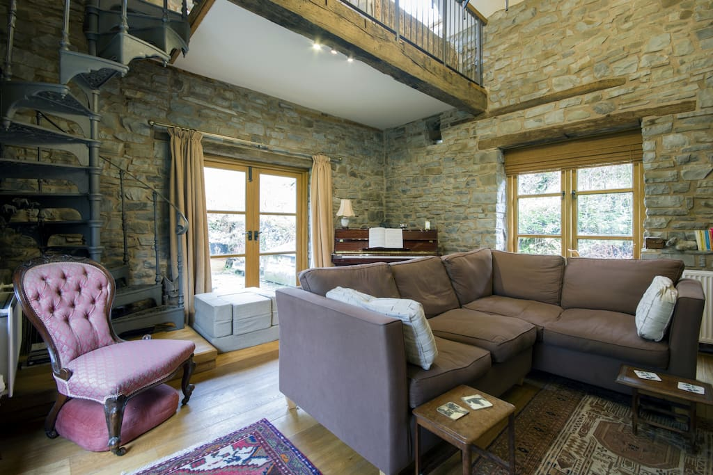 Living room or old Mill room. It has a mezzanine where there are two extra beds if needed. The French windows lead to a terrace which has access to the river and gardens.