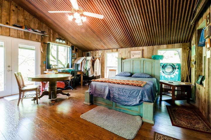 Upstairs - Queen bed, full bath, kitchenette and outdoor Deck under a tree canopy.