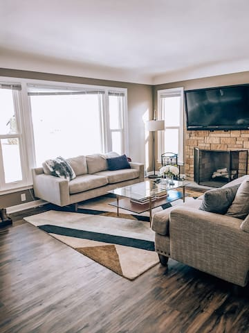 Sitting area with two couches, working fireplace, and large TV