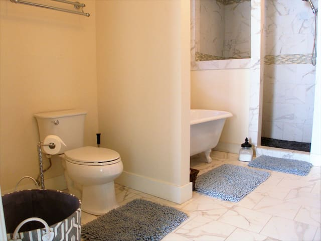 Very large Calcutta Gold Marble bath with sit down shower.