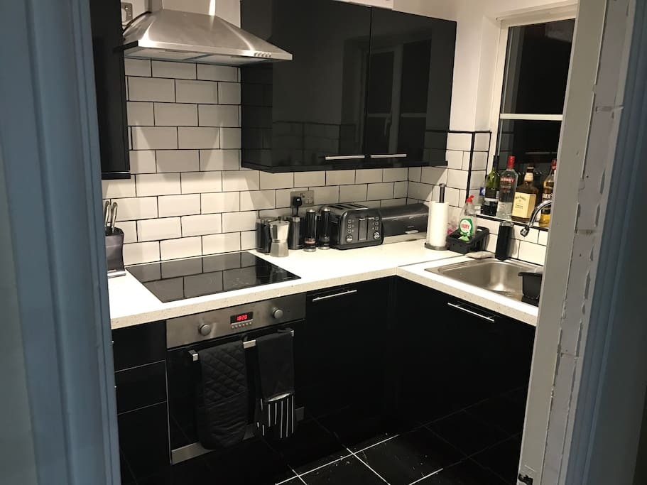 Modern kitchen with touch screen cooker and built in washing machine and fridge/freezer.