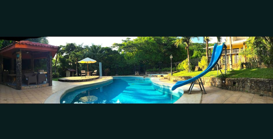 """Big pool with fun water slide, """"Ranchito"""" with BBQ, kids pool and lush gardens."""
