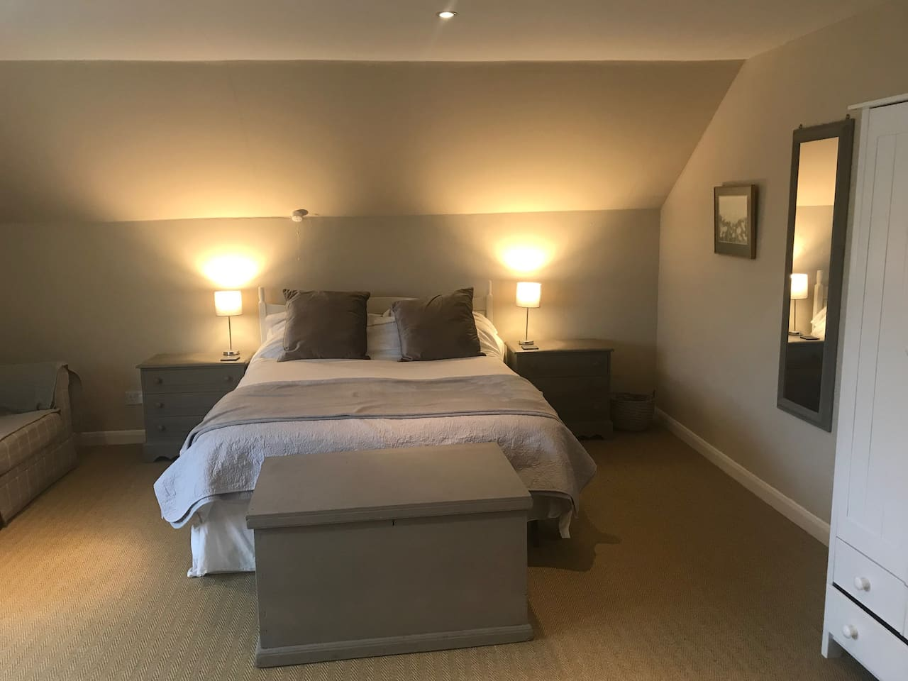 Large Bedroom with Double Bed, Wardrobe, Chest of Draws and Sofa.  A BabyBjörn Travel Cot and Single Toddler Mattress can also be provided for use in the Bedroom and/or sitting room if you are travelling with children.