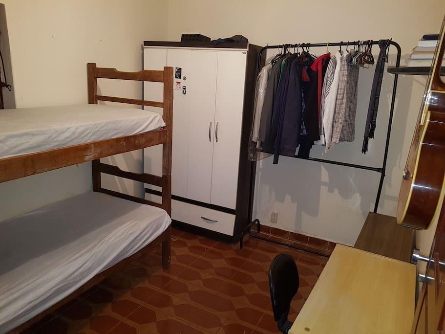 Quarto com beliche, cabides, mesa e guarda roupa