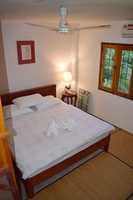 Birds eye view of your room with double bed king size, towels, extra pillows, bed-side table with lamp, ceiling fan and air-conditioning, glazed and bared windows
