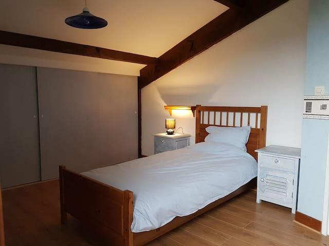 Une chambre simple à l'étage avec placard, donnant sur le balcon.